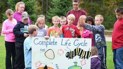 kids holding sign at audubon center