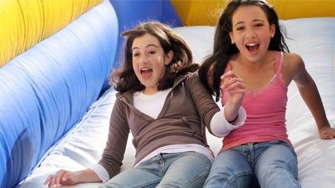 two girls sliding down bouncy slide