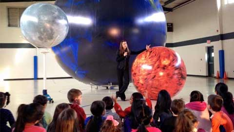 woman standing in front of large globe