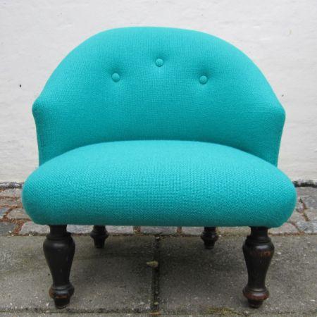Gammel lænestol med nyt tyrkis møbelstof, renoveret af Møbelværkstedet