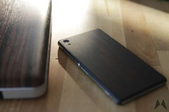 Xperia Z2 Mahagony Skin von dBrand neben einem Macbook inkl. Mahagony Skin von Slickwraps
