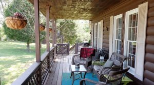 wooden patio with outdoor rug and furniture