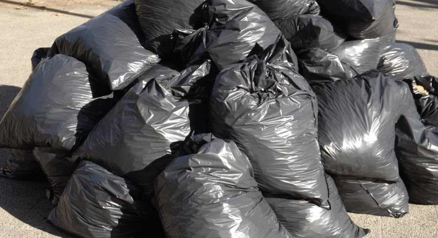 a pile of black bags of garbage