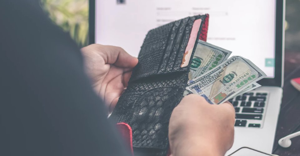 A man pulling out cash from his wallet