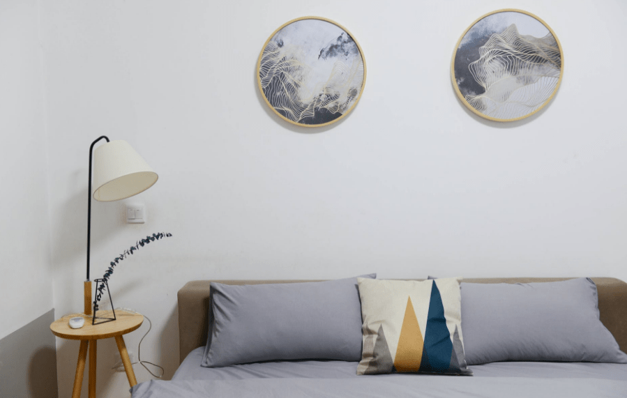 A bedroom with two round picture frames