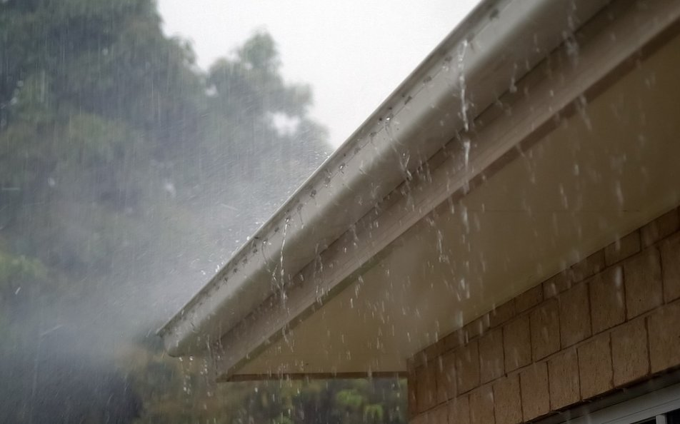 Roof gutter overflowing with rainwater