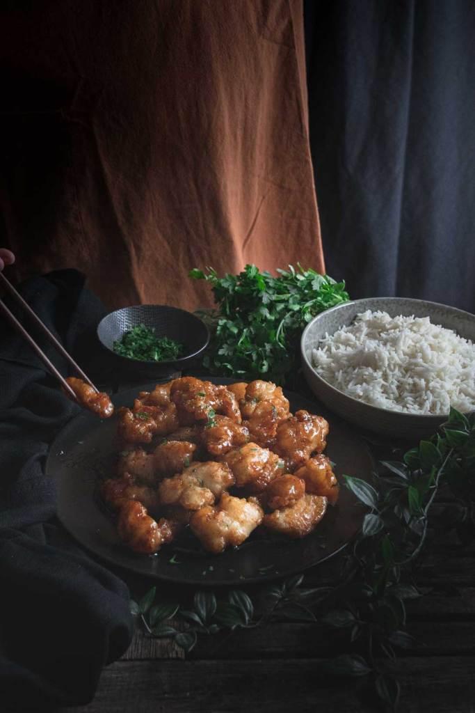Storytelling in der Foodphotographie: Stäbchen fassen ein Stück Honey Glazed Chicken
