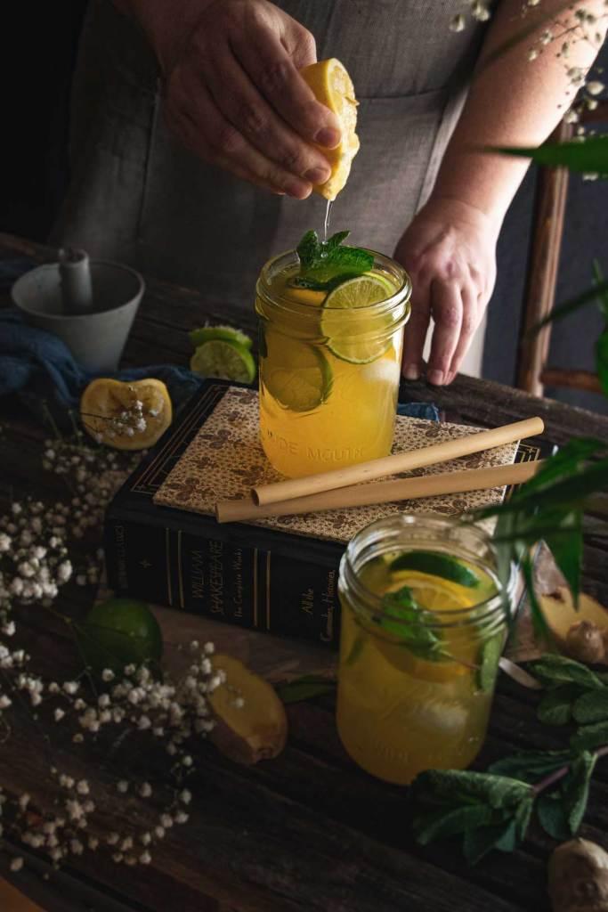 Storytelling in der Foodfotografie: Eine Hand quetscht eine Zitrone in ein Glas Eistee