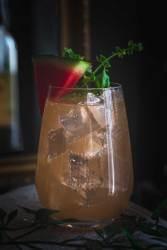 Ein Glas mit Melonen-Basilikum-Sirup Saft