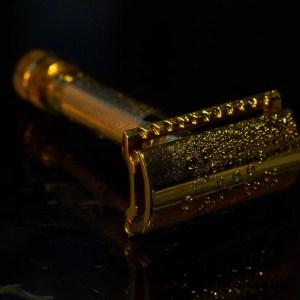 gold merkur safety razor on black background