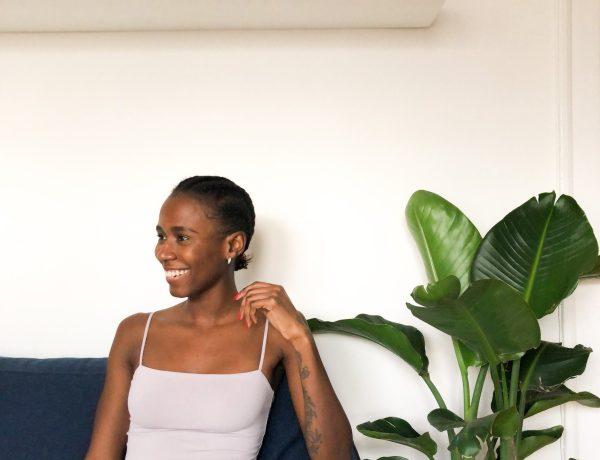 Omotola Akinbiyi sitting on blue cough against white background
