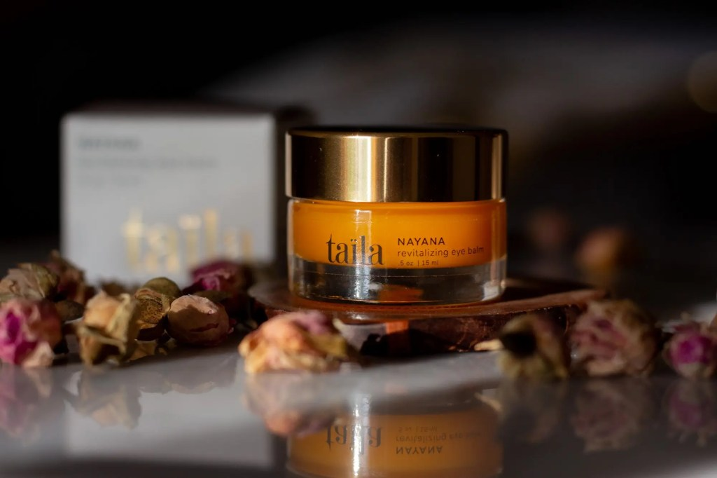 South Asian woman-owned Ayurvedic beauty brand Taila's Nayana Eye Balm on black background amidst dried roses