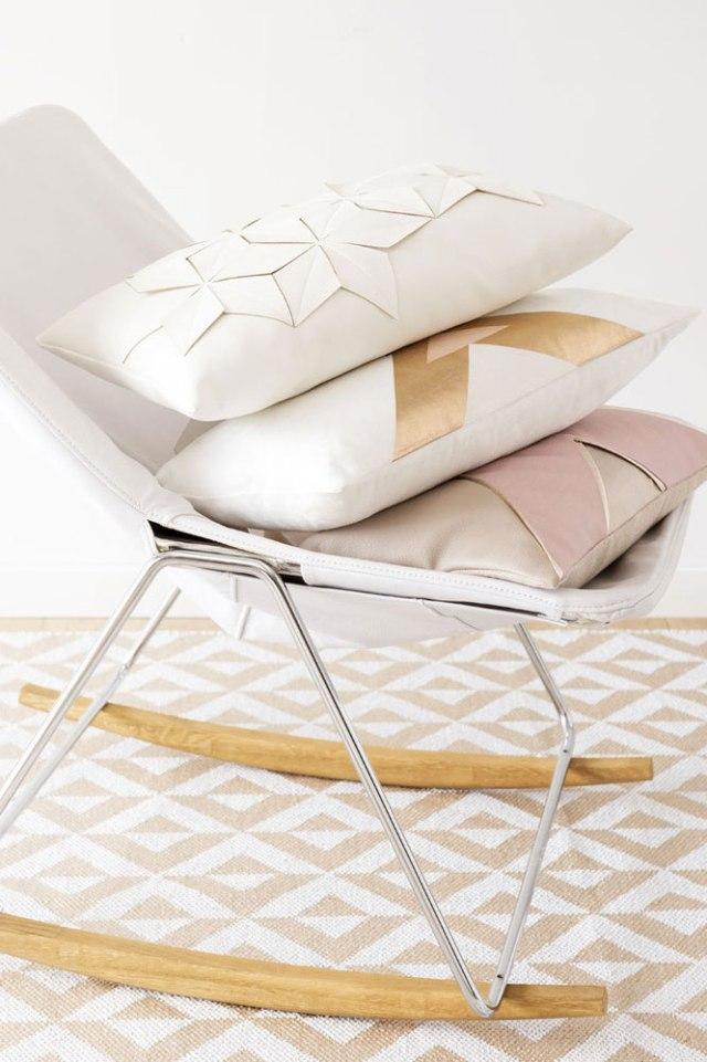 Sedia a dondolo con cuscini geometrici bianco, oro e rosa.