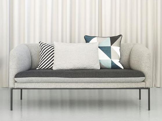 Divano grigio con composizione di cuscini geometrici colori freddi.