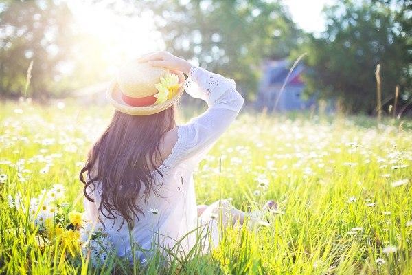 Giardino in primavera con ragazza sull'erba.