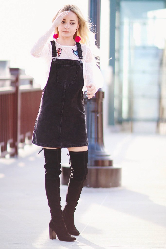 Alena Gidenko of modaprints.com styles a black overalls dress with over the knee boots