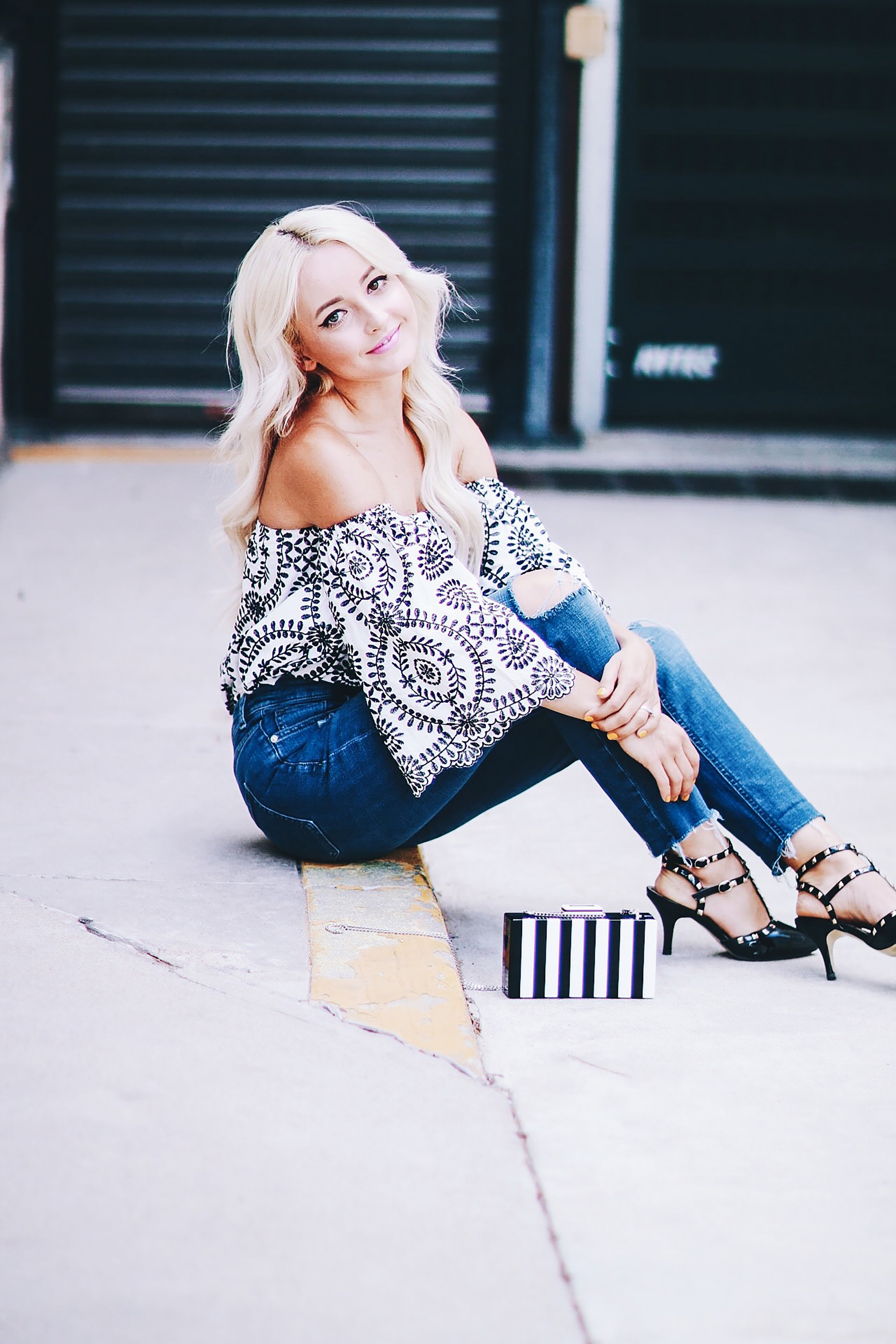 Alena Gidenko of modaprints.com styles an off the shoulder printed top with boyfriend jeans and studded black heels