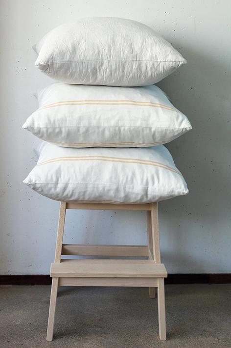 Modarium afbeelding van witte kussens op houten kruk tegen witte wand