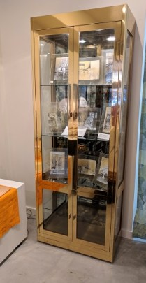 Mastercraft vintage vitrine. Brass and glass. Smoked mirrored glass in behind shelves. Interior lights with dimmer. 2200.-