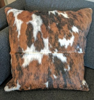 "Cow hide and leather pillow. Down and feather insert. 19"" square. 150.-"