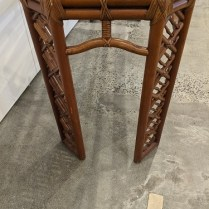 Detail of side of vintage Brown Jordan indoor rattan console table.