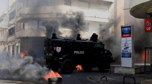 A security forces vehicle drive past burning tyres in capital, Dakar