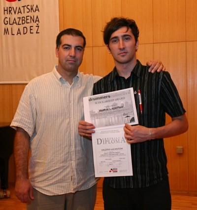 Petar Curic presents camper Valerio Lucantoni a scholarship to study at Drummers Collective in New York.