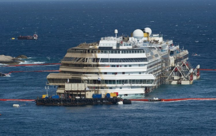 ISOLA DEL GIGLIO, ITALY - SEPTEMBER 17: The stricken Costa Concordia is upright after the parbuckling operation was succesfully completed around 4 am on September 17, 2013 in Isola del Giglio, Italy. Work began yesterday to right the stricken Costa Concordia vessel, which sank on January 12, 2012. If the operation is successful, it will then be towed away and scrapped. The procedure, known as parbuckling, has never been carried out on a vessel as large as Costa Concordia before. (Photo by Marco Secchi/Getty Images)