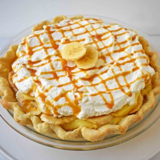 Salted Caramel Banana Cream Pie. Sweet Homemade Custard topped with fresh bananas, handcrafted salted caramel, and sweetened whipped cream all on a flaky, buttery crust.