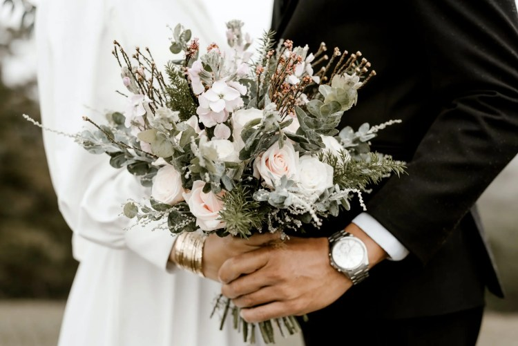 Eco wedding flowers. The image depicts a bride and groom holding a bouquet