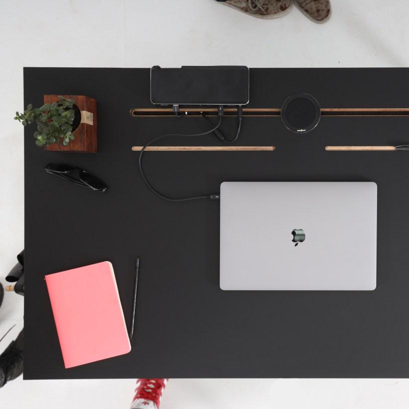 Površina crnog radnog stola Conform Desk sa prikazom utora za kabliranje