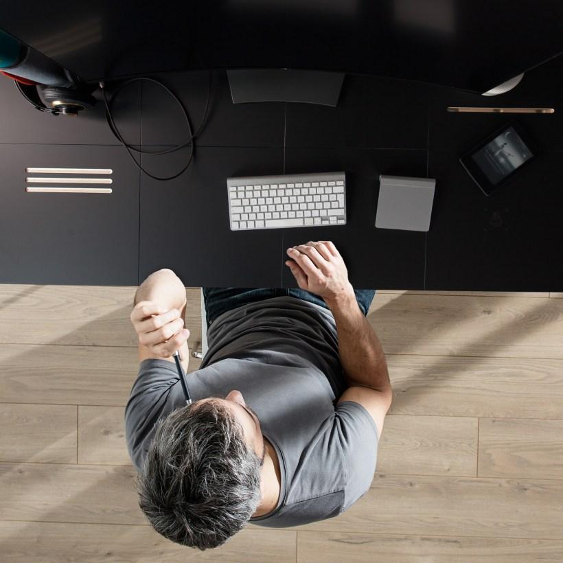 Osoba radi za Modular - modularnim radnim stolom crne površine, shutterstock montaža
