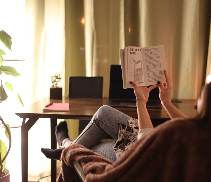 Djevojka sjedi na fotelji i čita knjigu, a ispred nje je smeđi radni stol Conform Desk