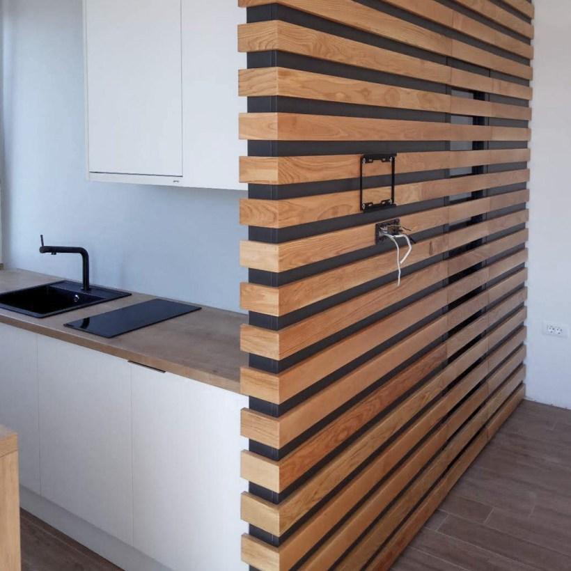 Čajna apartmanska kuhinja odvojena pregradnim zidom obučenim u drveni raster