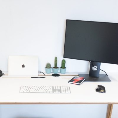Površina radnog stola Conform Desk White s monitorom, laptopom i tipkovnicom.