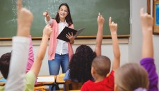 Teacher pointing to student, many students have hands raised