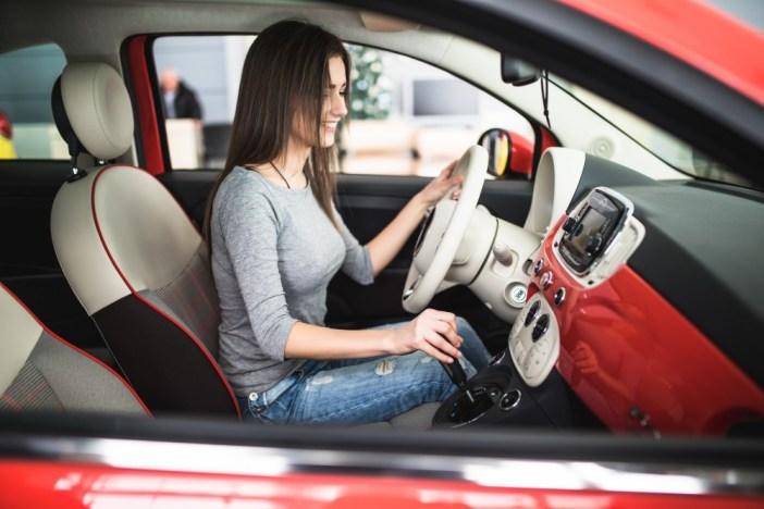 kobieta-pierwszy-raz-jedzie-nowym-samochodem-usmiehca-sie