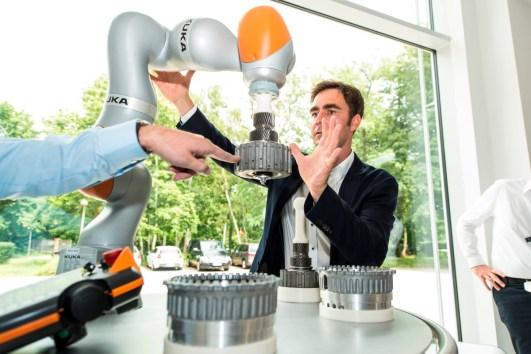Ein Werksleiter demonstriert diesen neuen, leichten Kuka-Roboter, der durch Kraftsensoren fühlen kann. Er lässt sich vom Menschen führen. Aber er hat keine Ethikbremse, sondern ist rund. Das ist die sinnvollere Verletzungsprävention.