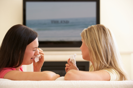 Two Women Watching Sad Movie On Widescreen TV At Home