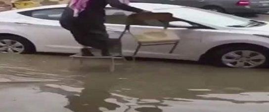 """بالفيديو.. حيلة ذكية لمعلم تنقذه من """"مياه الأمطار"""" للوصول إلى مركبته بحفر الباطن"""