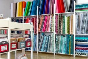 Bunte Auswahl an verschiedenen Jerseystoffen für Kinder und Erwachsene im Regal, farblich sortiert.