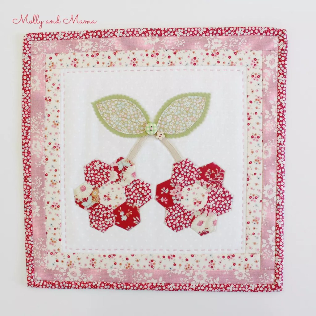 A cherry hexie mini quilt by Molly and Mama