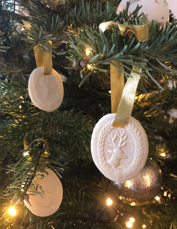 Springerle Cookies a traditional Alsace Lorraine Cookie with an intricate design on top hanging on a Christmas tree
