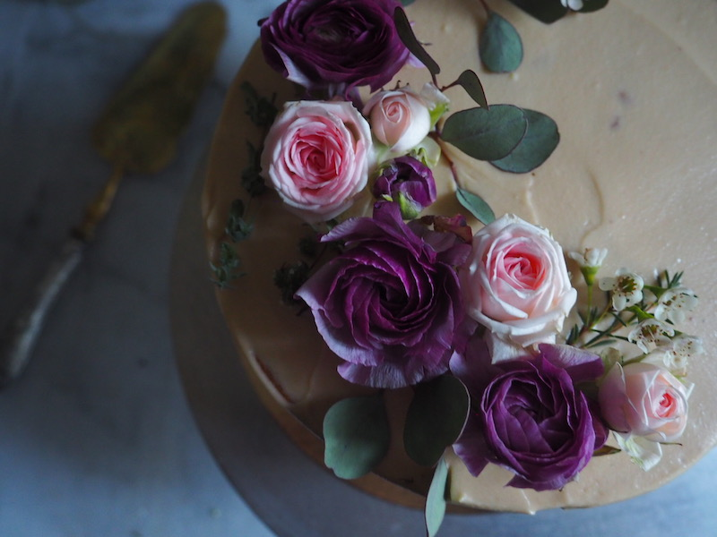 Pear Cake with Salted Caramel Mascarpone Frosting decorated with fresh flowers close up of the roses