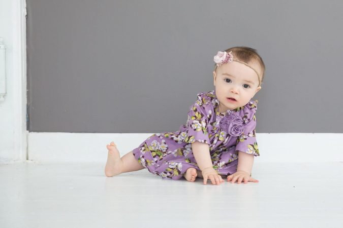 Baby Socks that Stay on, girl baby in purple flowered dress and no socks on