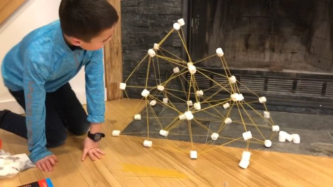 boy building a tower out of spaghetti and marshmallows on a snow day indoors