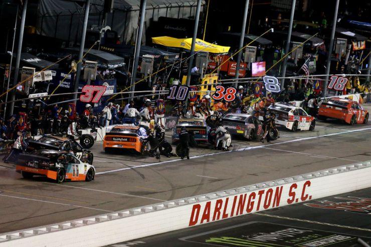Los coches de la NASCAR Cup Series en el carril de boxes durante una carrera en Darlington en 2019