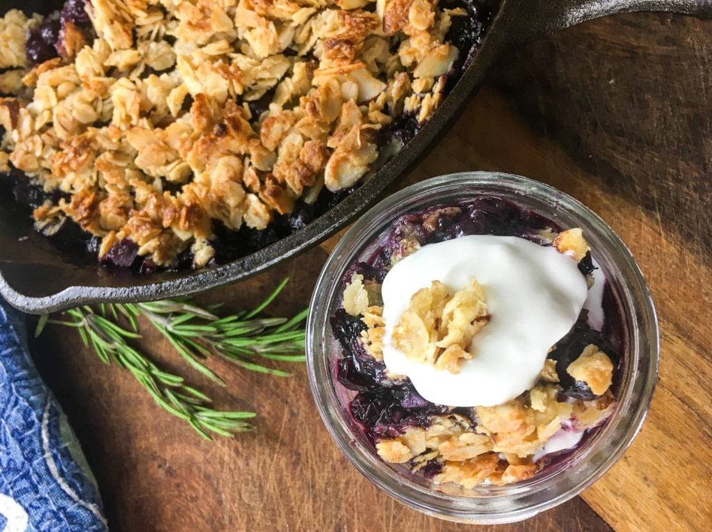 blueberry crisp in a cast iron pan with whipped cream