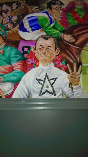 In the mural of all the winning Derby jockies, the artist turned this fellow into a 3-peat by modifying his fingers. Note he now has 7 fingers.