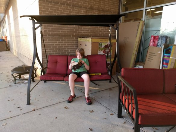 Getting a couple hours of reading in while waiting for his sisters.